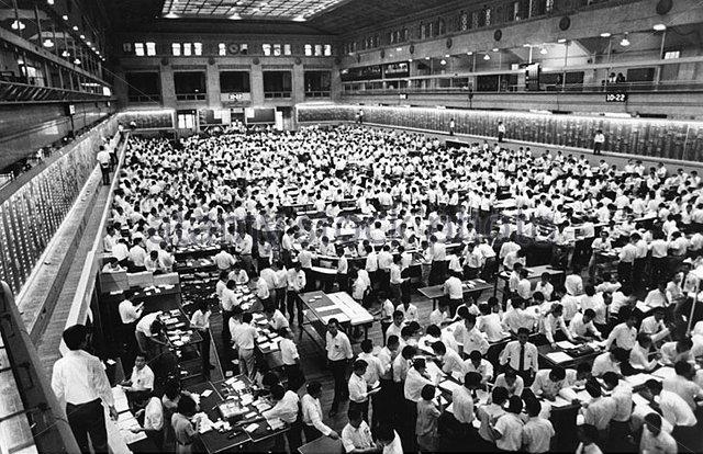 In werksituaties waar mannen onder elkaar zijn, zoals hier op de beursvloer in Tokio, gaat het jasje uit en stelt het (witte) shirt de mannen op (schijnbaar) gelijk niveau. Korte mouwen waren tot voor kort ongezien in een dergelijke situatie; liever rolde men de mouwen op.